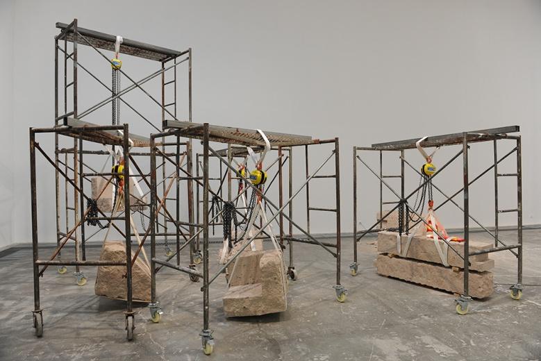 """香格纳北京邵一个展""""邵一在此"""",作品《亮灯工程》将汽车尾和凝灰岩,两种代表不同时间跨度和时代性的物并置、掺杂、镶嵌组合,带出了不稳定性和抽象性。"""