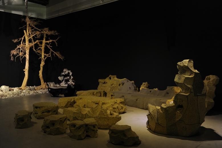 """史金淞空间站""""个人设计博""""北京现场,艺术家在""""设计""""与""""被设计""""之间博弈。作品《客厅里的园林》用聚氨酯泡沫做成的假山石与作品《双松木》一起构成了传统园林的假象。"""