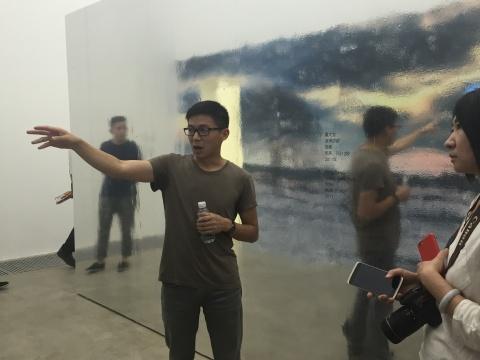"""苏文祥在现场导览""""闪灵"""",展墙是特地为展览打造而成,观众经过会如同在镜子前留下影像般,契合展览主题"""