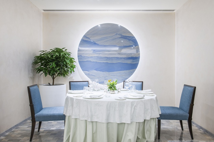 王府半岛酒店Jing餐厅一角,墙上的蓝白相间的作品与蓝椅子、白桌布相互印衬