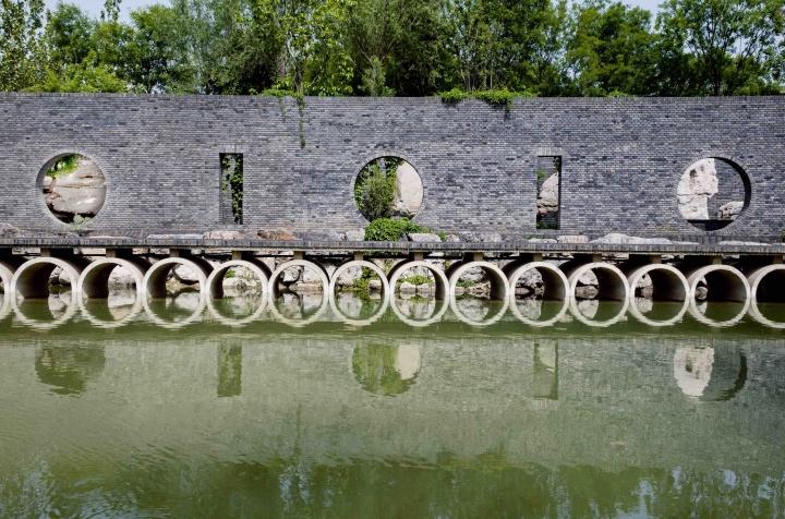 """红砖美术馆园林中的十七孔桥,背后""""门""""得形状则构成了红砖美术馆的logo。"""