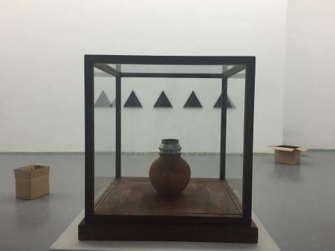 展览现场,近处为蔡东东的《罐子相机》,远处墙上为艺术家Jean-Charles Kien的《T1X5》,地面上的纸箱是马永锋的作品《分离的海洋》