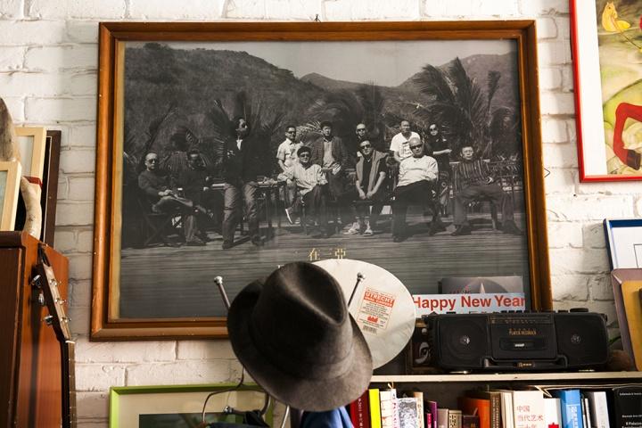墙上的照片,毛旭辉在后一排穿白色衣服。照片中还有张晓刚、王广义、吕澎等人。