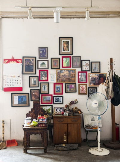 左侧的这张椅子,被毛旭辉画进作品中,成为一个经典的形象,毛旭辉说这张椅子在云南是非常普通的物件。椅子背后墙上挂的所有照片,都是毛旭辉感情所系