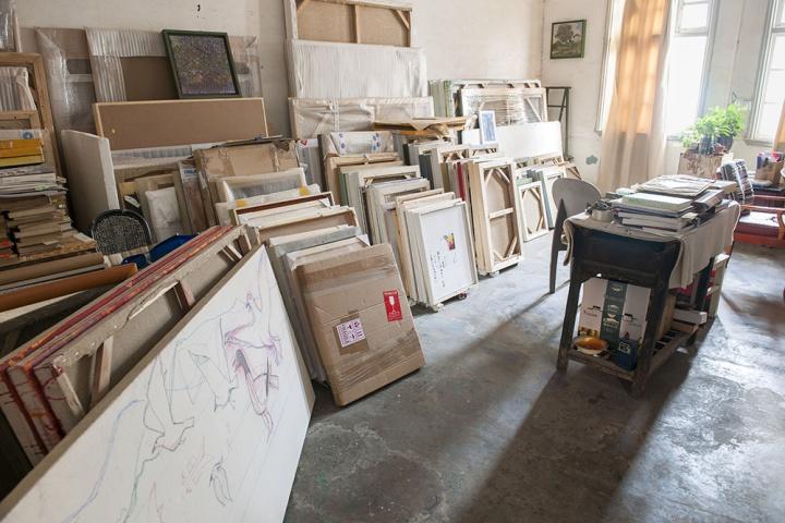 这个房间除了书柜和书桌,角落里摆满了毛旭辉的作品和书籍,可以看见作品的数量是非常多的,右侧的黑色桌子也显得很古老