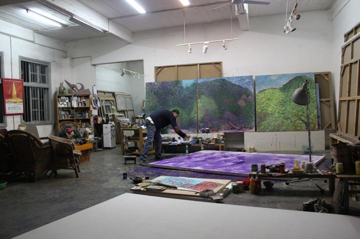 创作状态的毛旭辉,可以看见毛旭辉将画面平铺在地上进行创作