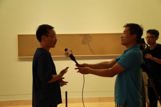 艺术家彭斯(左)在展览现场接受媒体采访