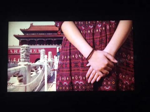 一个看似在镜头前拍照的女孩的肢体不断在画面中移动,不时的遮挡天安门和毛主席像。