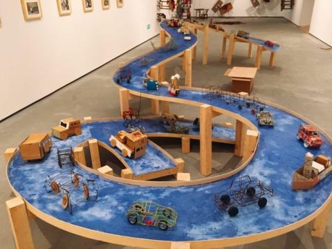 """《蓝色公路》木、肥皂、非洲儿童自制玩具,900x300x125cm,2003 2002年由于文化交流活动,我在刚果金沙萨驻留一个月。在六十年代的中国,我们的童年和此刻在金沙萨的非洲儿童一样,只能玩自制的玩具。在这一个月的时间里,我和他们一起做了这些玩具,我用当地的芭蕉叶做了条船,并将玩具放在船上。当我问他们""""最想要的是什么""""时,孩子们回答:""""离开这个国家""""。当我回到欧洲后的一个展览中,我做了""""蓝色公路"""",并将非洲儿童们与我一起做的交通玩具放在上面。"""
