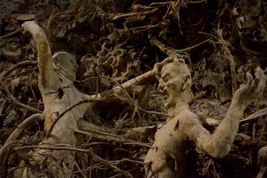乖张的或怪异的众生相嵌入泥土和树根中,相互缠绕