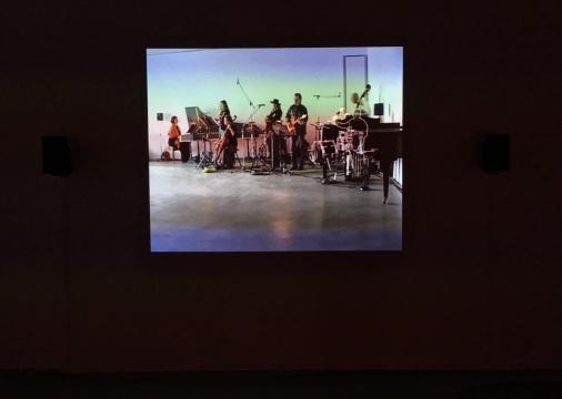 """安利·萨拉《Spurious Emission》时长7分30秒 录像投影  影片中,一群看似歌手或者演奏家的人聚集在一起弹奏,而钢琴前,一个用白线手绘勾勒的鬼魅般的""""鼓手""""正在配合着节奏敲打架子鼓。不同风格的音乐相互干扰。据说,作者最初的创作灵感是因为自己所处的现实环境:每日里高速公路休息处大货车的经过会干扰汽车中的广播讯号,导致不同频道相互切换。于是他便让一群专业的音乐家一本正经的模仿日常生活中失控的场景,模糊生活与表演的界限。然而叫人设问的是,如果这是创作的初衷,那么那个手绘白线勾勒的""""鬼魂"""",到底是意味着不自知的存在力,还是意味着现实里与可见和可知完全同在的另一个镜像维度中的存在力呢?"""