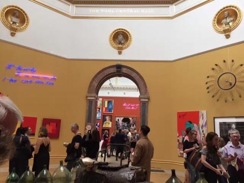 """2017伦敦皇家美术学院夏季展现场      到了今天,这个理念得到了进一步扩大。在夏季展览上,不光有老牌艺术家、年轻艺术家,也有不以艺术为职业、仅以此为爱好的素人艺术家。所有作品现场都可交易,对很多参展人来说,夏季展览是普通人体验一把当职业艺术家和艺术赞助人是什么感觉的机会。    夏季展览每年1月开始面向全国征集,层层选拔,最后甄选出1/10 的作品进入正式展览。当然,选拔过程仍带有""""美协式""""的傲慢:在世职业艺术家每人最多可展出2件作品;80名皇家美术学院成员却可以每人展出8件作品;再加上展览委员会邀请的特约艺术家,算下来,以2017年参展的1200件作品为例,超过半数来自皇家美术学院成员和他们选择的职业艺术家。听起来不怎么让人兴奋是不是?但我们从积极的方面想,这样的比例一定程度上保证了展览的严肃面貌;另一方面,也向公众展示了""""专业人士眼中的艺术是什么样的""""。这对缝合艺术从业者和普通人之间对艺术理解的裂痕是有帮助的,毕竟也是在加强彼此的了解嘛。    走进皇家美院,首先是非裔英国艺术家Shonibare的彩色雕塑""""Wind Sculpture V1"""";"""