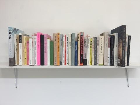 """秦观伟把自己书架上关于艺术理论、批评、策展等方面的书按他设计的次序排放于书架,书名从左至右阅读起来就像一个关于当代艺术的""""前世今生""""的故事。"""