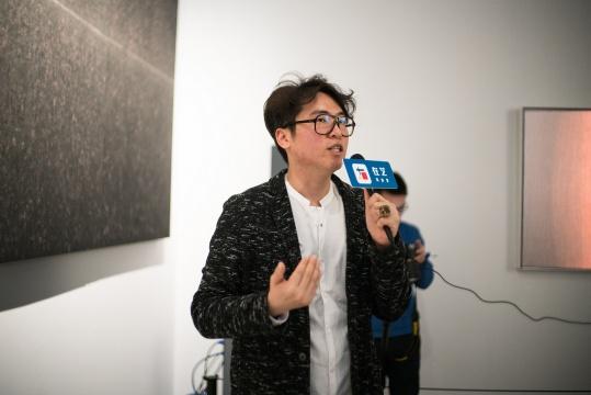 奥永美学艺术总监赖骏杰在展览现场,田卫作品前做导览