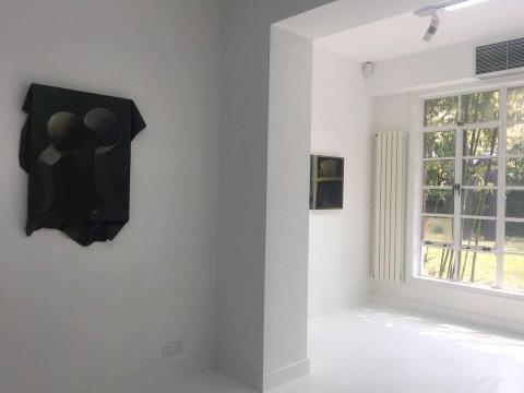 左侧的绘画作品《愿景》与窗外庭院里的雕塑呼应