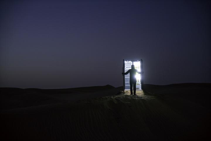 """2015年10月,赵赵在新疆开始实施《塔克拉玛干计划》,全程耗时23天。他和30余人的工作团队,从北京出发,带着100公里长的四芯电缆和一台冰箱,行驶近4000公里,抵达塔克拉玛干沙漠北端的小镇轮台。赵赵和镇上一家维吾尔农户协商,通过付费的方式,接通电源。接下来,他沿着沙漠公路的边缘,穿过一片胡杨林,朝着且末方向往南走,用改装后的""""探路者号""""沙漠车,10台变压器,在沙漠中铺设100公里的电缆,直至抵达塔克拉玛干沙漠的中心地带。电缆尽头,一台装满新疆啤酒的双开门冰箱接通电源,在空旷无人的沙漠腹地运行24小时。7天后,这些电缆、变压器、冰箱一同运回北京"""