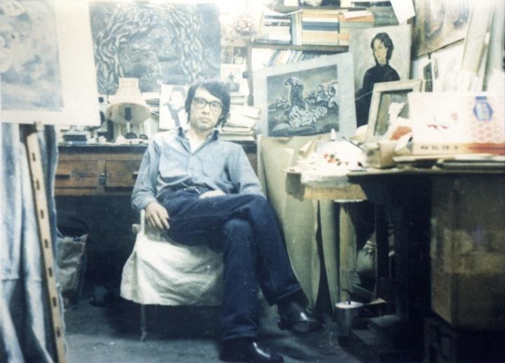 """1984年张晓刚在昆明歌舞团宿舍内,此时,刚从住了两个多月的医院出来,正在创作""""幽灵系列""""。身后的两幅作品是:《充满色彩的幽灵:向边缘移动》、《充满色彩的幽灵:初生的幽灵》。"""