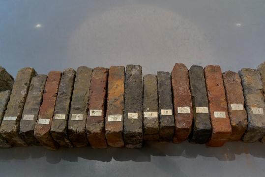 易连,《砖头们奇遇记》,2011,装置,建筑砖头,金属铭牌  金杜艺术中心入口处便摆放着一排砖头,每个砖头上都有编号