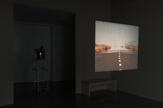 弗朗西斯·埃利斯《一个欺骗的故事,巴塔哥尼亚,阿根廷》,2003-2006年,银幕上是一条正发着热气的公路,而公路的另一边是一个闪闪发光的海市蜃楼
