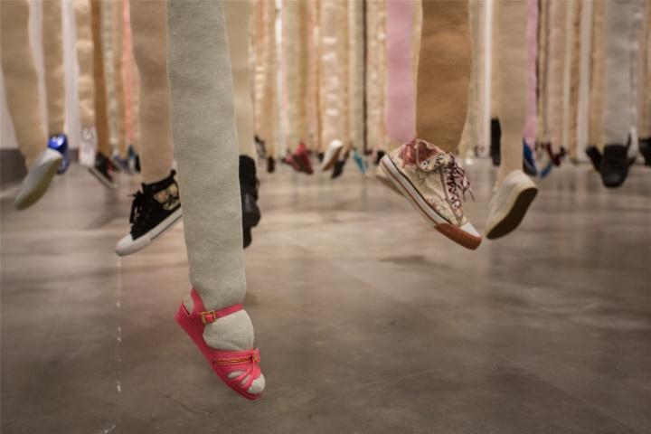 """作品《行思》银川当代美术馆现场  """"每双鞋被一条长长的织物'腿'相连,腿打结,悬挂。一只脚悬在空中可以看到鞋底,另一只脚,脚尖着地像在跳芭蕾。""""尹秀珍在自述中如此描述这件特别的作品。由500根颜色轻柔的织物串联的500双鞋,如树林一般疏密有致地悬置在展厅。随着空气的流动或观众的进入,它们也不时地轻微晃动。有人感受到了温馨,也有人觉察出了一丝惧怕。"""