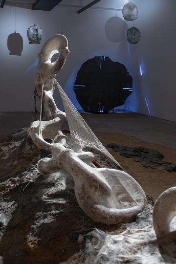 """《命运》 180×1250×350cm丝、茧、铁板、铁粉、油桶、聚氨酯树脂、丙烯、黄砂2012-201430年来,梁绍基潜心在艺术与生物学,装置与雕塑、新媒体、行为的临界点上进行探索,创造了以蚕的生命历程为媒介、以与自然互动为特征、以时间、生命为核心的""""自然系列""""。他的作品充满冥想、哲思和诗性,并成为虚透丝迹的内在美。"""