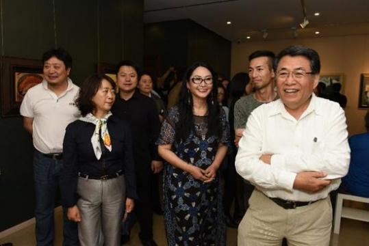 中国油画院院长杨飞云(左五),中国油画院画家芃芃(左二) 中国油画院画家秦先生(左一) 中国油画院画家黄远鹏(左三),中国油画画家尤勇(左四)与参展画家段威观看画展
