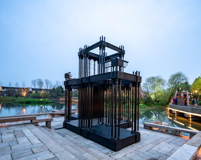 詹姆斯·贝克特(James Beckett,英国)《宫殿废墟》 7220×3500×5750cm装置 2016 作品位置:木心美术馆旁水榭平台 《宫殿废墟》是对阿姆斯特丹勤民宫的前身——1929 年被付之一炬的荷兰水晶宫的重构。贝克特的装置用燃烧中的断壁残垣的形式,再造了这一时刻的情景——一半像恐怖屋,一半像纪念碑。