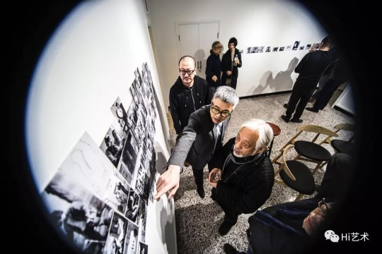 外交公寓12号空间的起点始于2015年12月对艺术家冯国东的一场纪念活动,这个活动将原本不是用于艺术展览的空间转变成了一个展览空间。展览现场呈现了大量历史图片档案和一组他在宋庄即兴创作的二锅头酒杯,同时播放了纪录片《快乐的苍蝇》。图为批评家栗宪庭在参观展览