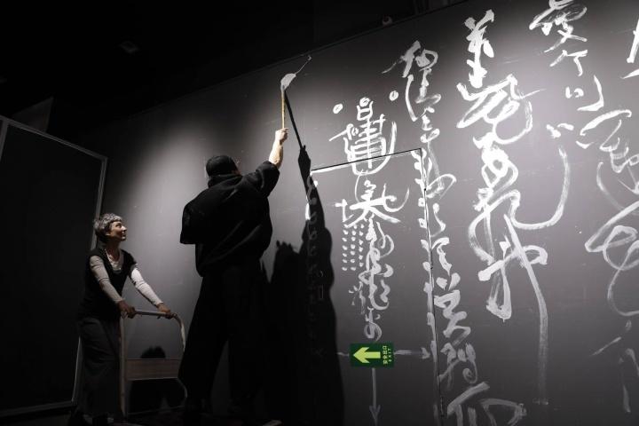 """展厅的一面墙上写的""""扫黑除恶""""的标语,以及鲁大东在开幕当天的现场书写"""