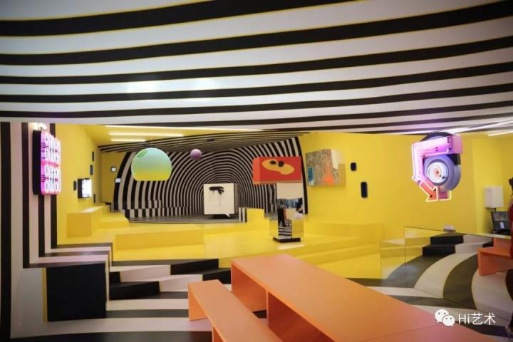Tobias Rehberger《有时候你就是可以称之为你自己的地方》425×877×250cm 咖啡厅与展览空间由两件霓虹灯、桌子与长凳组成 2018,图片由艺术家,釜山当代美术馆及纽格赫姆施耐德(柏林)惠允