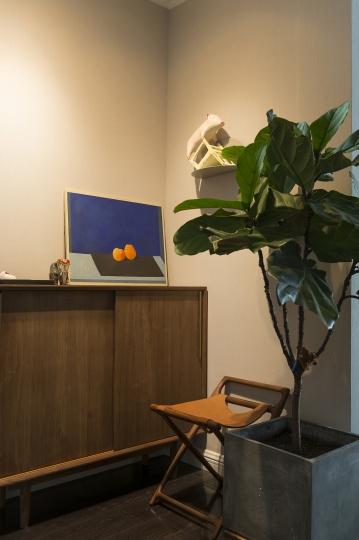 入口玄关处鞋柜上是崔金德的 《回忆的时光2》,墙上的小猪雕塑是张弱的衍生品