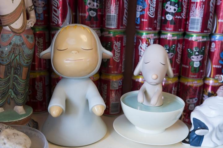 """奈良美智的""""梦游娃娃""""和""""梦游狗狗"""",它们身后是罗小虎搜集的各种纪念版可口可乐"""