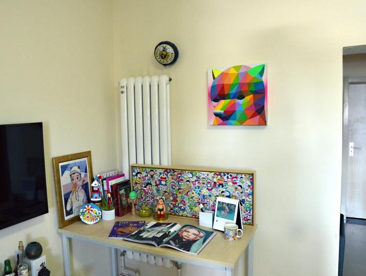 墙上是Okuda San Miguel画的《猪熊》,桌上正面立着的是村上隆的布画,左侧则是毛壮委托儿力力创作的卡通形象,现在也是他的微信头像