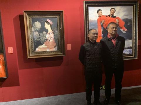 艺术家王沂东(右)与来宾在其作品前
