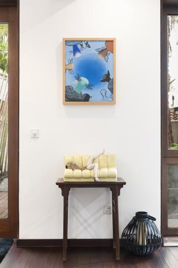 """条案上摆放的是刘建华90年代末的""""彩塑系列""""《迷恋的记忆》,墙上挂的是李山2003年的布面水彩作品《无题》。"""
