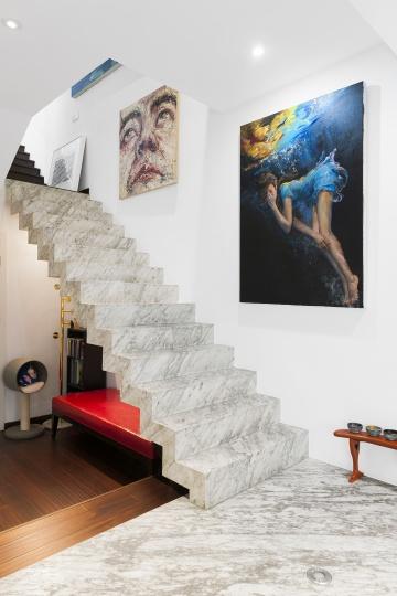连接一楼和二楼的是一整块大理石做成的悬浮状楼梯,墙上是喻红2014年的作品《天体》(右)和曾梵志的自画像(左)。