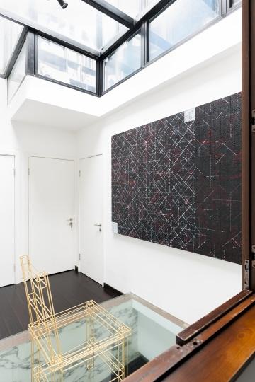 """天井的空间墙面也充分利用,右侧是丁乙的作品,玻璃地板上摆放的是高伟刚金色的""""椅子""""。"""
