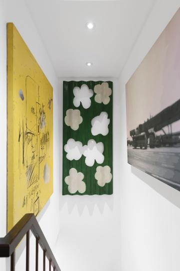 中间是王兴伟2003画在瓦楞板上的作品《华》,右侧是颜磊2002年的作品《上升空间之机场》,左侧是娄申义的作品《明天见》。