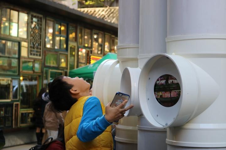小朋友好奇地与朱涛的作品《(潜望塔)全景柱》互动