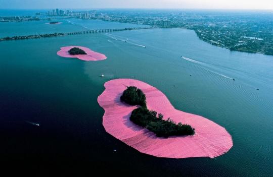 克里斯托夫妇(克里斯托与让娜·克劳德Jeanne-Claude 1935-2009下同)《环绕群岛》美国比斯坎湾 1980-83 摄影:Shunk-Kender © 1983 Christo   艺术家用60万平方米的粉红色织物把美国迈阿密比斯坎湾上的11座小岛包围。