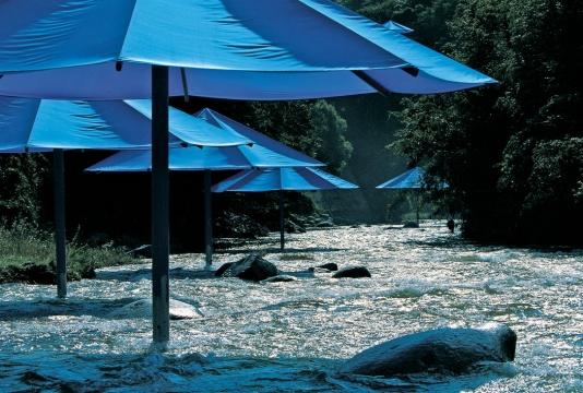 《伞》美国、日本1984-91摄影:Wolfgang Volz©1991Christo  明黄色的伞在美国,与美国加州的枯草干岩形成统一;蓝色的伞在日本,与东京河谷的滋润温暖呼应。