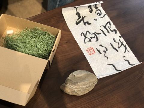 """开幕前,艺术家任芷田在直播平台进行了一场导览。他为观众准备了一份特别的礼物,是他在大自然中捡到的""""一块石头"""",这块石头存在于大自然中或许没有什么特别,但捡它回来源自天然的本能,如同他写的这几个字——""""慧眼识之,善缘得之"""""""