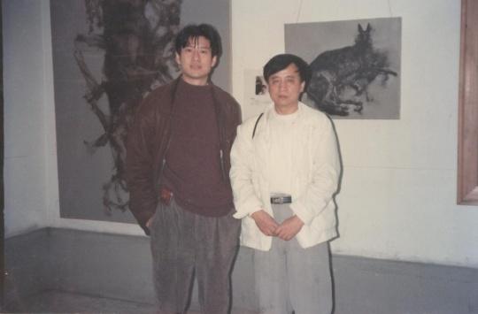 周春芽(左一)在其作品《黑根一家》与《躺着的黑根》之前,'96上海(美术)双年展展览现场,1996年。周春芽供图。