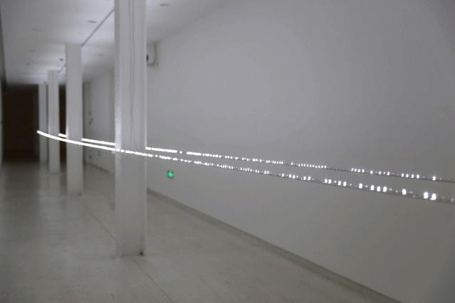艺术家将展厅走廊这一常被忽视的空间利用起来,用上千个闪烁的频率不同的LED灯管将其点亮,远远看去,像一条银色的地平线,作品本身完美嵌入美术馆建筑中。  《LED地平线》24.3×1×0.5m闪烁白色LED模组、铜焊丝不锈钢丝、不锈钢砝码、不锈钢结构、电源、电线 2020