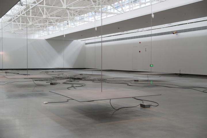 《电磁装置》是艺术家使用磁力、红外线、钢板和钢丝吊装而成的一件作品,当观众靠近的时候,红外线感应器会感应到人体的温度,控制箱便开始快速开合流向磁铁的电流,使钢板产生共振,导致钢板发声。当场馆里每个人在不同位置的时候,则会形成一种奇妙的音景。《电磁装置》尺寸可变 喷砂钢板、不锈钢杆、电磁铁、控制器、磁铁驱动器、红外传感器、电源 1997
