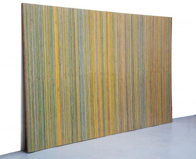 《一块多层板的反转》122×200×17cm 复合多层板、彩铅 2016  艺术家把一整张多层板以它的厚度 1.8 厘米为宽度标准进行切割,再把锯开的木条反转重新拼合成一块整板,并按它本身的纹层涂上不同的颜色。从而使一块物理意义上没有太大变化的多层板从概念到视觉实现了整体的翻转。